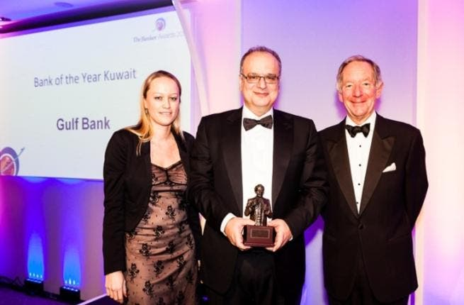 Mr. Michel Accad, Chief Executive Officer at Gulf Bank accepting the 'Bank of the Year' award from Melissa Hancock, Middle East Editor of 'The Banker' and Michael Buerk, Former BBC news presenter during the awards ceremony in London