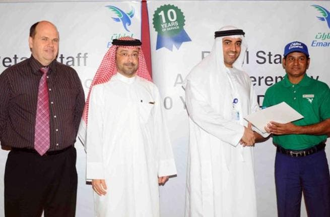 Dr. Rahma honors a staff member in the presence of Abdulla Al Noman, and Darren Smith