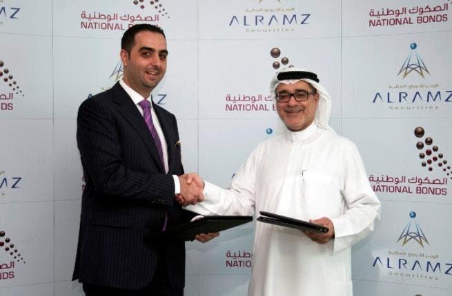 Mohammad Murtada Al Dandashi, Partner and Managing Director, Al Ramz Securities and Mohammed Qasim Al Ali, CEO of National Bonds Corporation shaking hands