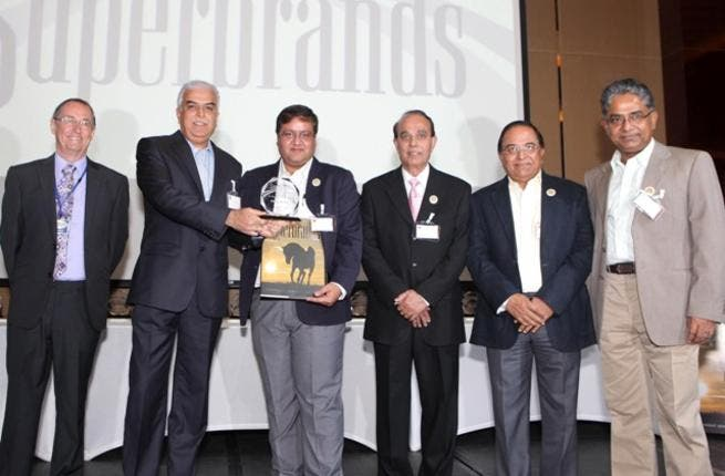 Mike English, Director of SuperBrands ME handing the award to Niranjan Gidwani, Deputy CEO of Eros Group