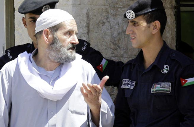 Omar Othman, the father of radical Islamist cleric Abu Qatada, speaks with Jordanian policemen outside the state security court in Amman on July 7, 2013 (Source: AFP/KHALIL MAZRAAWI)