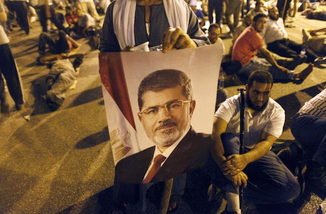An Egyptian supporter of the Muslim Brotherhood holds a portrait of deposed president Mohamed Morsi during a rally outside Cairo's Rabaa al-Adawiya mosque late on July 7, 2013. (Source: AFP/MAHMOUD KHALED)