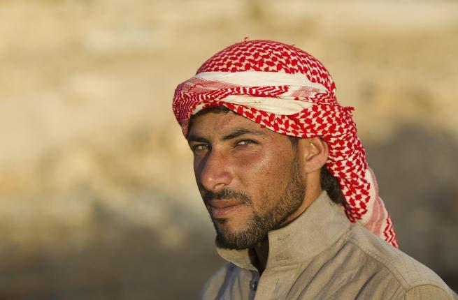 Bedouin camel herder wears a shemagh at sunset in Jordan (Shutterstock/Martin Good)