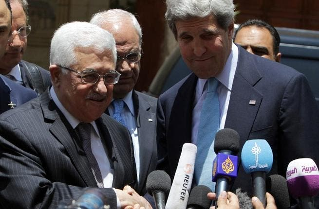US Secretary of State John Kerry and Palestinian president Mahmoud Abbas shake hands as they speak to the press following their meeting at the Palestinian presidential compound in the West Bank city of Ramallah (Abbas Momani / AFP)