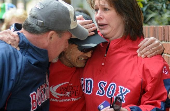 Runner crying when he finds friends after two explosions at the Boston Marathon finish line (AFP/ John Mottern)