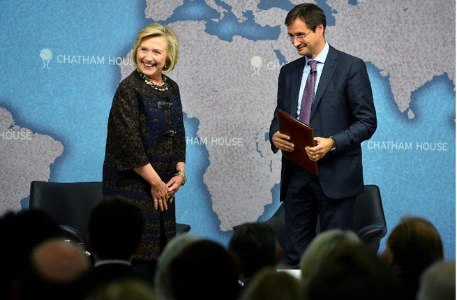 Former US secretary of state Hillary Clinton and director of Chatham House Robin Niblett (R) arrive for a discussuion session at Chatham House in central London on October 11, 2013. (Image credit: AFP)