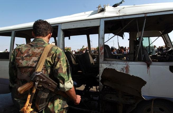 YEMEN, SANAA : Yemeni security forces inspect a damaged military bus following a bomb blast in Sanaa on August 25, 2013. AFP PHOTO/ MOHAMMED HUWAIS