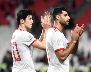 Iran's forward Sardar Azmoun (L) and Iran's midfielder Mehdi Taremi greets the fans following their victory during the 2019 AFC Asian Cup Round of 16 football match between Iran and Oman at the Mohammed Bin Zayed Stadium in Abu Dhabi on January 20, 2019.