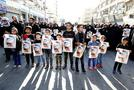 Iranian boys hold images of one of the victims Mohammad Taha Eghdami, 4, during a public funeral ceremony for those killed during an attack on a military parade on the weekend. (ATTA KENARE / AFP)