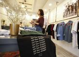 """Palestinian fashion designer Yasmeen Mjalli speaks while standing in her clothing shop where her label collection """"BabyFist"""" carrying anti-sexual harassment slogans is showcased, in Ramallah in the occupied West Bank  ABBAS MOMANI / AFP"""