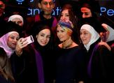 Syria's First Lady Asma al-Assad (centre) poses for a picture during a graduation ceremony of future teachers of a Syrian Organisation for Persons with Disabilities, in Damascus yesterday (Twitter)