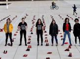 Israelis walk past an installation of red shoes during a rally against domestic violence in the Israeli coastal city of Tel Aviv on December 4, 2018 (Twitter)