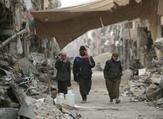 سوريون يسيرون وسط الدمار في مدينة الرقة