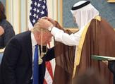 الملك سلمان خلال الباسه قلادة لدونالد ترامب خلال زيارة الاخير للسعودية