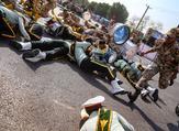 On September 22, 2018 in the southwestern Iranian city of Ahvaz shows a soldier running past injured comrades lying on the ground at the scene of an attack on a military parade. (AFP/File)