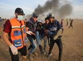 Palestinian paramedics and journalists carry a wounded fellow journalist during clashes with Israeli forces east of Gaza city. (Said KHATIB / AFP)