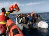 A member of Spanish humanitarian NGO Proactiva Open Arms, throws life jackets to refugees and migrants during a rescue operation off the coast of Libya on October 3, 2016. (AFP / Aris Messinis)