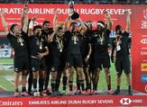 New Zealand's players celebrate with the trophy of the Men's Sevens World Rugby Dubai Series Cup after the Final match between USA an New Zealand on December 01, 2018. KARIM SAHIB / AFP
