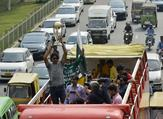 Pakistani cricketer Mohammad Irfan holds the 2019 ICC Cricket World Cup trophy atop a bus during a parade event in Lahore on October 3, 2018. The 2019 Cricket World Cup is the scheduled to be hosted by England and Wales from May 30th to July 14th of 2019. ARIF ALI / AFP