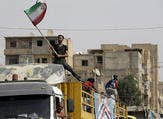 A Syrian man holds the Iranian flag as a convoy carrying aid provided by Iran arrives in the eastern city of Deir Ezzor. (LOUAI BESHARA/ AFP)