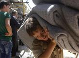 A child in the Syrian town of Douma in the Eastern Ghouta region near Damascus carries blankets distributed by relief workers and the United Nations on July 26, 2018 (AFP/File)