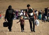 Syrians walk carrying their belongings after crossing the Syria-Jordan border. (AFP)