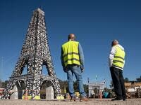 """Yellow Vest"" movement protestors look at a 11,5 meter Eiffel Tower replica they made of 135 wood pallets on the roundabout of Le Luc, southeastern France. (AFP/ File Photo)"