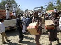 Yemenis carry boxes of food aid provided by the UAE Red Crescent for displaced people in the city of Marib. (Abdullah Al Qadry / AFP)
