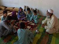 In this photograph taken on May 3, 2019, Afghan man Hamisha Gul 65, looks as his disabled children eat breakfast in their house in the Khogyani district of Nangarhar province. NOORULLAH SHIRZADA / AFP