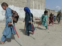 In this photograph taken on September 8, 2018, Afghan disabled children belonging to Hamisha Gul family who lost their legs following unexploded rocket explosion, walk outside their house after a class in Khogyani the district of Nangarhar province. NOORULLAH SHIRZADA / AFP