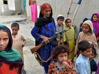 In this photograph taken on April 22, 2019, Afghan woman Niaz Bibi (C in blue),70, holds a weapon as she stands among her orphaned children and grandchildren at their home in the Kot district of the Nangarhar province. NOORULLAH SHIRZADA / AFP