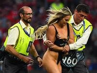 Stewards escort a pitch invader during the UEFA Champions League final football match between Liverpool and Tottenham Hotspur at the Wanda Metropolitano Stadium in Madrid on June 1, 2019.  GABRIEL BOUYS / AFP