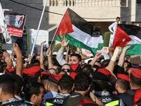 "Protesters wave Palestinian (C) and Jordanian (R) flags as they chant slogans during the ""March of Anger"" demonstration leading to the US Embassy in the Jordanian capital Amman on June 21, 2019, against the US President's ""Deal of the Century"" and the US-led Middle East economic conference in Bahrain.  Khalil MAZRAAWI / AFP"