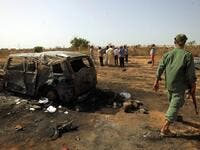 Libyans inspect the site of a car bomb attack that targeted servicemen during the funeral of an ex-army commander in the Libyan city of Benghazi (AFP)