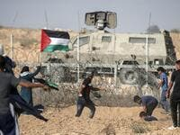 Palestinian demonstrators throw stones at Israeli security forces during protests along the border with Israel, east of Khan Yunis, in the southern Gaza Strip on July 12, 2019. (MAHMUD HAMS / AFP)