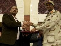 Sudanese deputy chief of the ruling miliary council Mohamed Hamdan Dagalo (R) and protest movement Alliance for Freedom and Changes leader Ahmad al-Rabiah shake hands after inking an agreement before African Union and Ethiopian mediators in Khartoum early on July 17, 2019. (AFP/ File Photo)