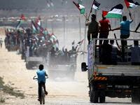 Palestinian demonstrators wave their national flag as they drive towards the border fence with Israel, east of Gaza City on July 22, 2019. (MOHAMMED ABED / AFP)