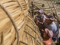 Members of the crew assemble the 14-meter long sailing reed boat Abora IV in the town of Beloslav, Bulgaria, on July 25, 2019. NIKOLAY DOYCHINOV / AFP