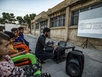 "A member of Syrian-Kurdish filmmaker Shero Hinde's mobile cinema ""Komina Film"" initiative prepares a laptop connected to a projector and screen for a film screening for children at a school yard in the village of Shaghir Bazar, 55 kilometres southest of Qamishli in the Kurdish-populated areas of northeastern Syria's Hasakeh province, on July 28, 2019. DELIL SOULEIMAN / AFP"