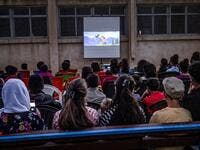 "Children attend a film screening as part of the mobile cinema ""Komina Film"" initiative organised by Syrian-Kurdish filmmaker Shero Hinde, at a school yard in the village of Shaghir Bazar, 55 kilometres southest of Qamishli in the Kurdish-populated areas of northeastern Syria's Hasakeh province, on July 28, 2019.  DELIL SOULEIMAN / AFP"