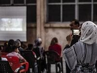 "A woman uses a cell phone to shoot a video of children attending a film screening as part of the mobile cinema ""Komina Film"" initiative organised by Syrian-Kurdish filmmaker Shero Hinde, at a school yard in the village of Shaghir Bazar, 55 kilometres southest of Qamishli in the Kurdish-populated areas of northeastern Syria's Hasakeh province, on July 28, 2019. DELIL SOULEIMAN / AFP"