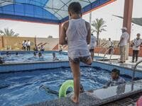 A Palestinian amputee child prepares to jump into the pool during a summer camp origanized by the Palestinian Children's Relief Fund (PCRF) in the town of Khan Yunis in the southern Gaza strip on August 3, 2019. SAID KHATIB / AFP