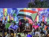 Sudanese protesters sit in front of a recently painted mural during a demonstration near the army headquarters in the capital Khartoum. (AFP)