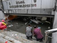 Shop owners look at their belongings in a flooded undergate shop center on August 17, 2019 in Eminonu district in Istanbul, after a heavy rainfall. Turkey's mega city Istanbul was lashed by a heavy rainstorm on August 17, killing a homeless man and leaving parts of the historic Grand Bazaar flooded.  Ozan KOSE / AFP