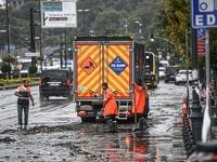 Municipality employees work on the road in Eminonu district, Istanbul, after a heavy rainfall, on August 17, 2019. Turkey's mega city Istanbul was lashed by a heavy rainstorm on August 17, killing a homeless man and leaving parts of the historic Grand Bazaar flooded.  Ozan KOSE / AFP
