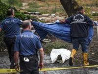 Turkish police officers cover a body on the ground in Eminonu district, Istanbul, after a heavy rainfall, on August 17, 2019. Turkey's mega city Istanbul was lashed by a heavy rainstorm on August 17, killing a homeless man and leaving parts of the historic Grand Bazaar flooded.  Ozan KOSE / AFP