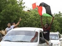 A Sudanese man waves a national flag as people celebrate outside the Friendship Hall in the capital Khartoum where generals and protest leaders signed a historic transitional constitution meant to pave the way for civilian rule in Sudan, on August 17, 2019. (AFP/ File Photo)