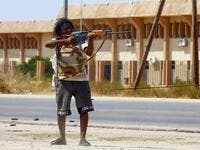 A fighter loyal to the internationally-recognised Government of National Accord (GNA) points his gun toward enemy lines during clashes with forces loyal to strongman Khalifa Haftar, in Espiaa. (AFP/ File Photo)