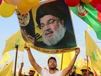 Supporters of the Lebanese Shiite Hezbollah movement carry ballons, party flags and a photograph of the movement's leader Hasan Nasrallah, in the town of Al-Ain in Lebanon's Bekaa valley on August 25, 2019. (AFP/ File Photo)