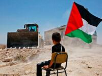 A Palestinian boy sits on a chair with a national flag as Israeli authorities demolish a school site in the village of Yatta, south of the West Bank city of Hebron and to be relocated in another area, on July 11 2018. (Hazem Bader/AFP / Getty Images)